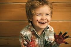 Lycklig unge som har gyckel Lyckligt le för pojkekonstnär på träväggen royaltyfri foto