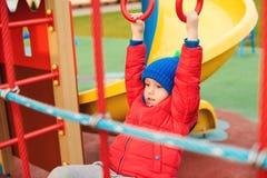 Lycklig unge som har gyckel på den utomhus- lekplatsen Gullig pys som bär varm kläder Roligt barn som utomhus spelar i kall höst royaltyfria bilder