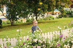 Lycklig unge som har gyckel utomhus- near vitt trästaket för litet pojkebarn Royaltyfri Fotografi