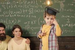 Lycklig unge som har gyckel Wunderkindbegrepp Smart barn, wunderkind i doktorand- lock som pekar på hans huvud Framlägga för pojk Royaltyfria Bilder