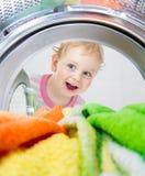Lycklig unge som ser den inre washmaskinen med kläder royaltyfria bilder