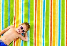 Lycklig unge som solbadar på den färgrika filten Royaltyfri Fotografi