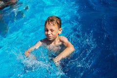 Lycklig unge som spelar i blått vatten av simbassängen på ett tropiskt r Arkivfoton