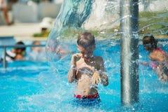 Lycklig unge som spelar i blått vatten av simbassängen på ett tropiskt r Royaltyfri Fotografi