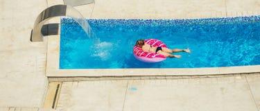 Lycklig unge som spelar i blått vatten av simbassängen på ett tropiskt r Royaltyfria Bilder