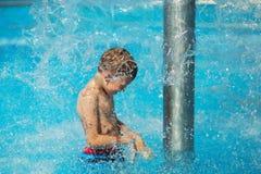 Lycklig unge som spelar i blått vatten av simbassängen på ett tropiskt r Royaltyfri Bild