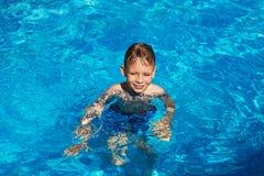 Lycklig unge som spelar i blått vatten av simbassängen på ett tropiskt r Royaltyfri Foto