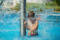 Lycklig unge som spelar i blått vatten av simbassängen på ett tropiskt r Arkivbilder