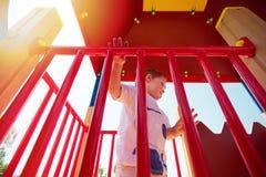 Lycklig unge som spelar lekar på färgrik lekplats royaltyfri fotografi