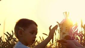 Lycklig unge som spelar med en liten träväderkvarn på solnedgången vete för sommar för dagfält varmt Begreppet av jordbruk och pl lager videofilmer