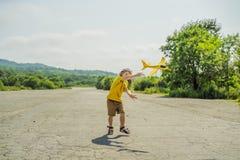 Lycklig unge som spelar med leksakflygplanet mot gammal landningsbanabakgrund Resa med ungebegrepp royaltyfria bilder