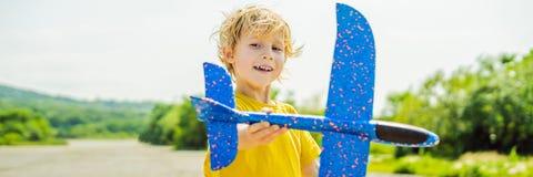 Lycklig unge som spelar med leksakflygplanet mot gammal landningsbanabakgrund Resa med ungebegreppsBANRET, LÅNGT FORMAT royaltyfria foton