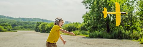 Lycklig unge som spelar med leksakflygplanet mot gammal landningsbanabakgrund Resa med ungebegreppsBANRET, LÅNGT FORMAT fotografering för bildbyråer
