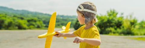 Lycklig unge som spelar med leksakflygplanet mot gammal landningsbanabakgrund Resa med ungebegreppsBANRET, LÅNGT FORMAT royaltyfria bilder