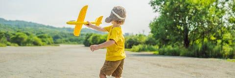 Lycklig unge som spelar med leksakflygplanet mot gammal landningsbanabakgrund Resa med ungebegreppsBANRET, LÅNGT FORMAT arkivfoto