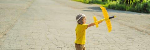 Lycklig unge som spelar med leksakflygplanet mot gammal landningsbanabakgrund Resa med ungebegreppsBANRET, LÅNGT FORMAT royaltyfri fotografi