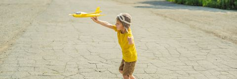 Lycklig unge som spelar med leksakflygplanet mot gammal landningsbanabakgrund Resa med ungebegreppsBANRET, LÅNGT FORMAT royaltyfri bild
