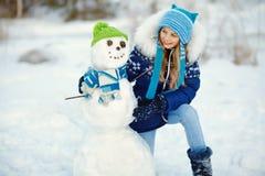 Lycklig unge som utomhus spelar med snögubben i vintern royaltyfria bilder