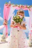 Lycklig ungeflicka i härlig klänning på tropisk bröllopsetu Royaltyfri Bild