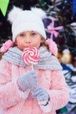lycklig ungeflicka med julgodisen Stående för vinterferie på julträdet fotografering för bildbyråer