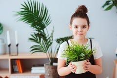 lycklig ungeflicka som tar omsorg av hemmastadda houseplants, iklädd stilfull svartvit dräkt Arkivfoto