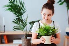 lycklig ungeflicka som tar omsorg av hemmastadda houseplants, iklädd stilfull svartvit dräkt Royaltyfri Bild