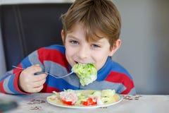 Lycklig ungepojke som äter ny sallad med tomaten, gurkan och olika grönsaker som mål eller mellanmålet Sunt barn som tycker om arkivfoto