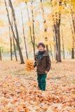 Lycklig ungepojke som går i parkera höstbakgrundscloseupen colors orange red för murgrönaleaf royaltyfria foton