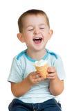 Lycklig ungepojke som äter glass i den isolerade studion Royaltyfri Fotografi