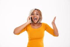 Lycklig upphetsad afrikansk amerikankvinna som talar på mobiltelefonen arkivbilder