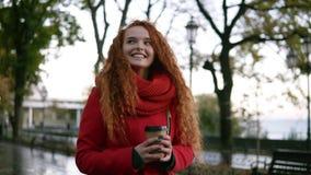 Lycklig upphetsad kvinna i rött lag som går med en takeaway drink i gatan i en regnig höst Ursnygg ung flicka med stock video