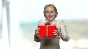 Lycklig upphetsad kvinna som rymmer den röda gåvaasken lager videofilmer
