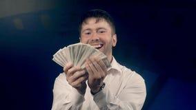 Lycklig upphetsad man som rymmer många sedlar i hans händer arkivfilmer