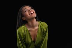 Lycklig upphetsad ung afrikansk amerikankvinna i grön badrock som skrattar över svart bakgrund Royaltyfri Bild