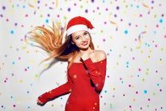 Lycklig upphetsad ung kvinna i Santa Claus hattdans och leende över vit bakgrund, flygconfitti Nätt flicka i röd klänning, l Royaltyfria Foton