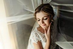 Lycklig ursnygg blond brud som får iklädd morgonen, smil royaltyfria foton