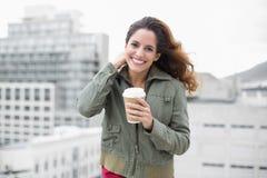 Lycklig ursnygg brunett i vintermode som rymmer den disponibla koppen Arkivfoton
