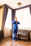 Lycklig ursnygg stilig brudgum som får klart iklätt morgonen på bakgrund av ett rum Royaltyfria Bilder