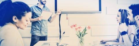Lycklig utövande geende presentation till kollegor i mötesrum på det idérika kontoret arkivfoton