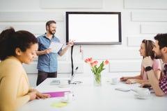 Lycklig utövande geende presentation till kollegor i mötesrum på det idérika kontoret arkivfoto