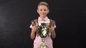 Lycklig utmärkelse för skolpojkeinnehavbunke som segrar sportturnering, lyckat barn stock video