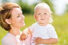 Lycklig utomhus- stående för moder- och litet barnson Royaltyfria Foton