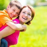 Lycklig utomhus- stående för moder och för son Arkivfoton