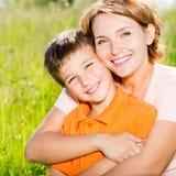 Lycklig utomhus- stående för moder och för son Arkivbilder