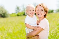 Lycklig utomhus- stående för moder- och litet barnson Arkivbild