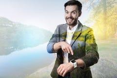 Lycklig uttrycksfull man som pekar till hans smarta klocka arkivbilder