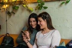 Lycklig vängrupp som ser en mobil på bryggeristångrestaurangen arkivfoton