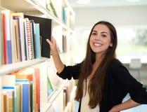 Lycklig vänlig kvinna som väljer en bok för att läsa royaltyfri fotografi