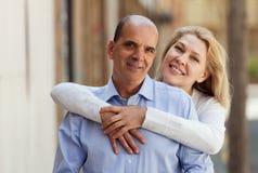 Lycklig vänpensionär med den mogna kvinnan som tillsammans kramar Arkivbild