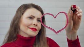 lycklig valentin för dag Flickan drar hjärtor på exponeringsglas med läppstift